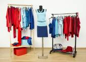 Wardrobe with red and blue clothes arranged on hangers. — Stock Photo