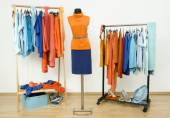 Wardrobe with complementary colors orange and blue clothes arranged on hangers. — Stock Photo