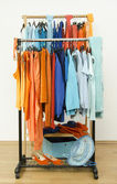 Wardrobe with complementary colors orange and blue clothes hanging on a rack nicely arranged. — Stock Photo
