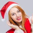 Beautiful young woman with Santa hat smiling looking happy surprised. — Stock Photo #60525975