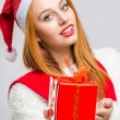 Beautiful young woman holding in front a Christmas present. — Stock Photo #60526027