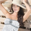 Beautiful girl with hat at the beach sitting on a lounge chair. — Stock Photo #74068891