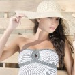 Beautiful girl with hat at the beach sitting on a lounge chair. — Stock Photo #74068897