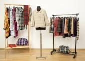 Dressing closet with plaid clothes arranged on hangers and a jacket on a mannequin. — Stock Photo