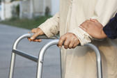 Senior woman using a walker cross street — Stock Photo