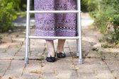 Anciana con un andador en casa. — Foto de Stock