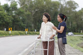 Senior woman using a walker cross street — Stock Photo