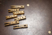 Wooden clothespins on a metal plate — Stock Photo