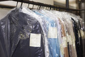 Dry cleaning things hanging in a row — Stockfoto
