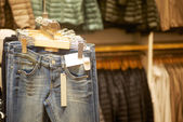 Row of hanged blue jeans in a shop — Stock Photo