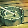 Metal ashtray with a cigarette on a table — Stock Photo #55962037