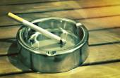 Metal ashtray with a cigarette on a table — Stock Photo