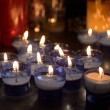 Firing candles in catholic church on dark background — Stock Photo #55970599