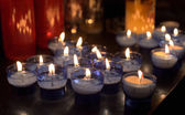 Firing candles in catholic church on dark background — Stock Photo