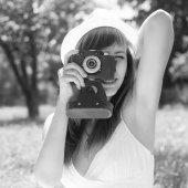 Giovane donna in posa con la vecchia fotocamera a pellicola nel parco estivo — Foto Stock