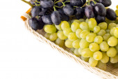 Different grapes varieties in wicker basket isolated on whire background — Stockfoto
