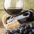 Cluster of fresh dark blue grapes with red wine in glass on wood background — Stock Photo #53409835