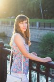 Young beautiful hipster woman waiting for somebody at the embankment — Stock Photo