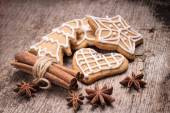 Christmas gingerbread cookies with various spices on wood background. — Stockfoto