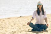 Young woman in white hat relaxe at the beach in summer midday — Stock Photo