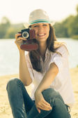 Young woman posing with old film camera. Caucasian hipster girl in hat — Stock Photo