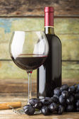 Winery background. Dark blue grapes with bottle of red wine — Stock Photo