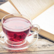 Glass cup of tea with old book on wood background — Stock Photo #54844975