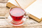 Glass mug with red karkade tea and opened book on background — Stock Photo
