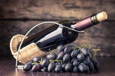 Winery background. Bottle of red wine with cluster of dark blue grapes on wooden table — Stock Photo