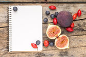 Fresh wild berries and figs with blank notebook on wood background — Stock Photo