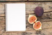 Fresh cut in half fig with blank paper notebook — Stock Photo