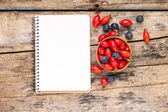 Fresh wild berries with paper notebook on wooden table. — Stock Photo