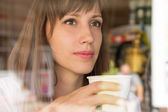 Young thinking woman with paper cup of coffee or tea — Stock Photo