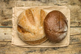 Loafs of different species of bread on wood background — Stock Photo