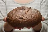 Fresh baked rye bread in female hand — Foto Stock