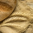 Fresh bread with wheat ears on wooden table. — Stock Photo #58853127