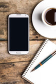 Smart phone with notebook and cup of strong coffee — Stockfoto