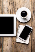 Mobile workplace with tablet PC, phone and cup of coffee — Stock Photo