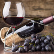 Winery background. Wineglass with bottle of red wine and cluster of grape — Stock Photo #66340139
