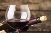 Red wine in wineglass against corked bottle — Stock Photo