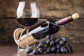 Winery background. Wineglass with bottle of red wine and cluster of grape — Stock Photo