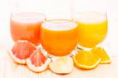 Different juice in glass with pieces of fresh fruits. — Stock Photo