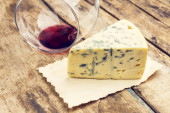 Blue cheese with overturned glass of wine — Stock Photo