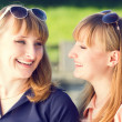 Young twins girls having fun laughing in summer park — Stock Photo #75389409
