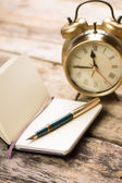 Open small notebook with fountain pen and old-fashioned alarm clock behind — Stock Photo