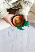 Cup of coffee in female hands, top view — Stock Photo