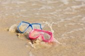 Fun water activity. two diving masks at the beach splashed by wa — Stock Photo