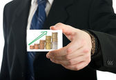 Businessman showing card with growing savings — Stock Photo