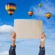 Hands holding banner with hot air balloon and blue sky backgroun — Stock Photo #56767793