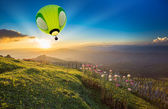 Hot air balloon over forest mountain at sunset — Stockfoto